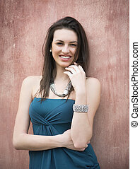 Smiling attractive young woman against red wall