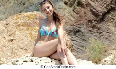 Smiling attractive young woman in a bikini sitting on a rock on the beach