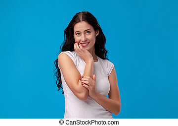 Smiling attractive young woman thinking on blue background