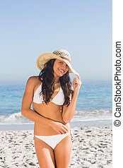 Smiling attractive young woman wearing straw hat posing