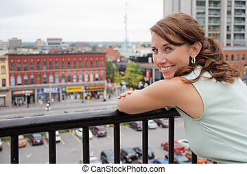 Smiling attractive young woman with city background looking at camera