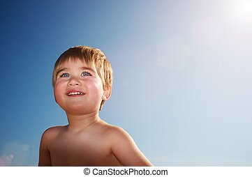 Smiling baby against blue sky.