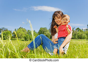 Smiling baby and his mother together in the meadow