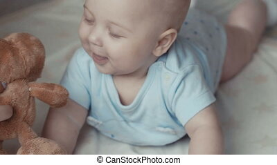 Smiling baby boy in white sunny bedroom.