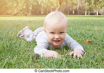 Smiling baby boy lying on the green grass outdoors