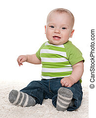 Smiling baby boy sits on the white carpet