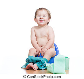 smiling baby boy sitting on chamber pot with toilet paper ...