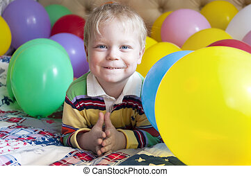 Smiling baby boy with balloons.