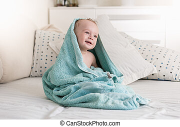 Smiling baby covered in blue towel after having bath