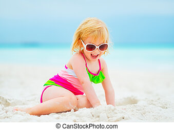 Smiling baby girl in sunglasses playing with sand on beach