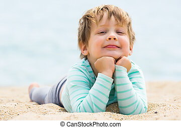 smiling baby girl laying on beach