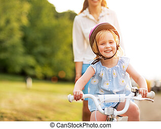 Smiling baby girl riding bicycle