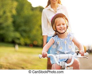 Smiling baby girl riding bicycle