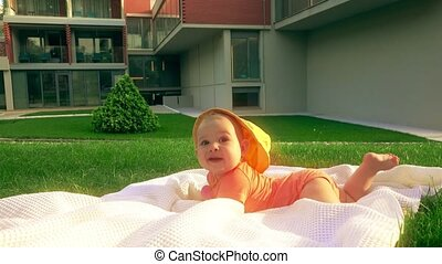 Smiling baby girl trying to crawl on the grass