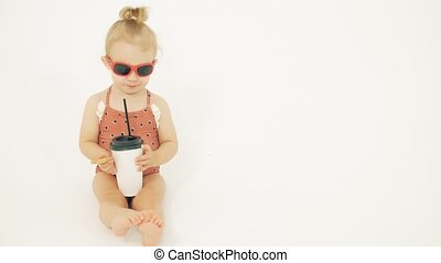 Smiling baby girl wearing sunglasses and swimsuit holds paper cup with a straw against white background