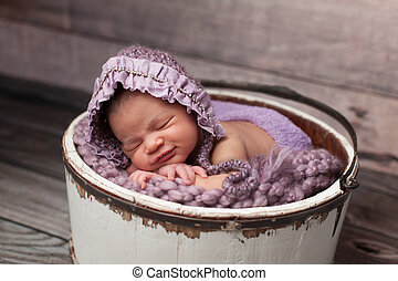 Smiling Baby Girl with Lilac Bonnet Sleeping in a Bucket -...