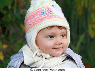 Smiling baby in white hat outdoor autumn background. Closeup portrait