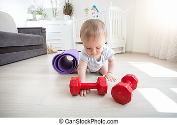 Smiling baby playing with dumbbells on floor at home