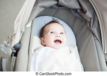 Smiling baby relaxing in a stroller