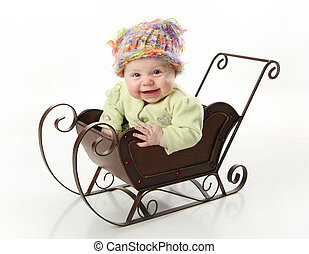Smiling baby sitting in a sled