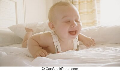 Smiling baby tries to crawl in sunny bedroom - Smiling baby...