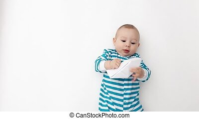 Smiling baby wearing blue striped romper plays with paper...