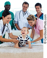 Smiling baby with a medical team in hospital