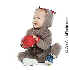 Smiling baby with Christmas ball looking on copy space