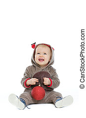 Smiling baby with Christmas ball looking up on copy space