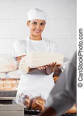 Smiling Baker Holding Bread Slices In Bakery