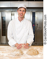 Smiling baker kneading dough in bakery