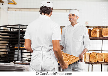 Smiling Baker's Carrying Bread Loaves In Tray