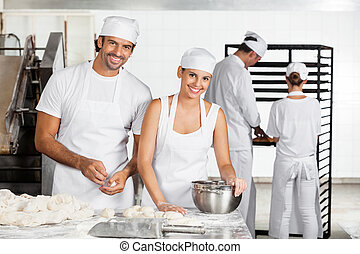 Smiling Baker's Making Dough Together In Bakery