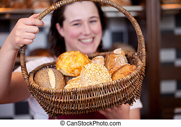 Smiling bakery worker with rolls in a basket