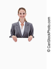Smiling bank employee holding blank sign in her hands