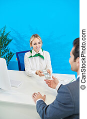 Smiling bank representative giving loan to businessman