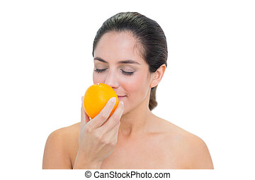 Smiling bare brunette smelling an orange