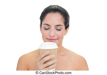 Smiling bare brunette smelling disposable cup