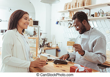 Smiling barista carrying out payment procedure