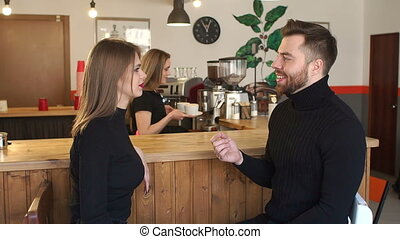 Smiling Barista girl serves to a young couple a Cup of coffee in a coffee shop.