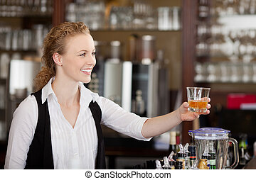Smiling barmaid serving alcohol
