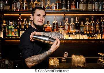 Smiling bartender standing on the background of the bar shaking a cocktail