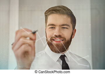Smiling bearded businessman working with futuristic screen and drawing diagrams