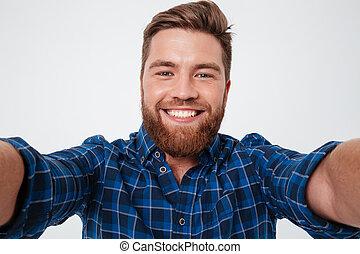 Smiling bearded man in checkered shirt making selfie over...