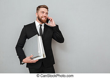 Smiling bearded man in suit talking on the smartphone