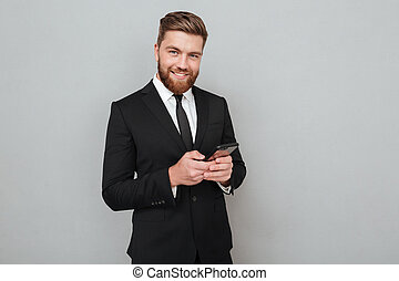 Smiling bearded man in suit using his smartphone