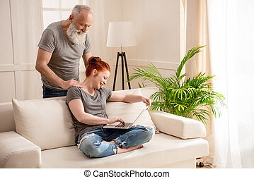 Smiling bearded man looking at beautiful mature woman using laptop on couch
