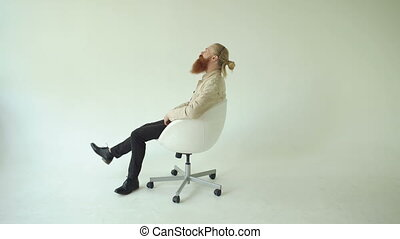 Smiling bearded man turning on swivel office chair on white...