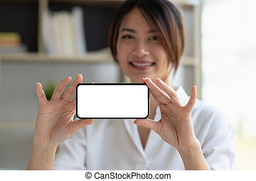 Smiling beautiful asian businesswoman showing blank smartphone monitor, with copyspace area for slogan or text message.