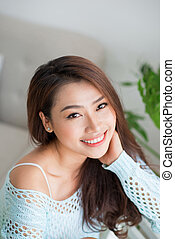Smiling beautiful asian woman relaxing in the morning sitting indoors.